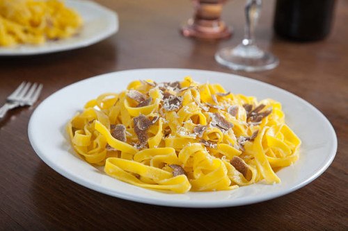 typical Italian pasta with truffle slices and parmesan cheese